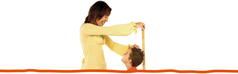 A mother measuring the height of her son.